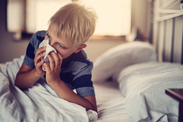 sick little boy lying in bed and blowing nose - infezione respiratoria foto e immagini stock