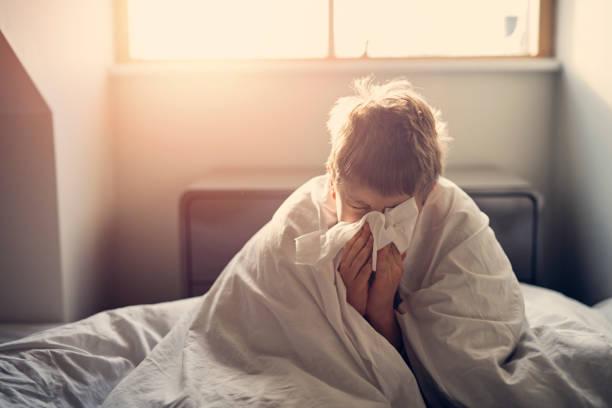 больной маленький мальчик, лежащий в постели и дующий носом - болезнь стоковые фото и изображения