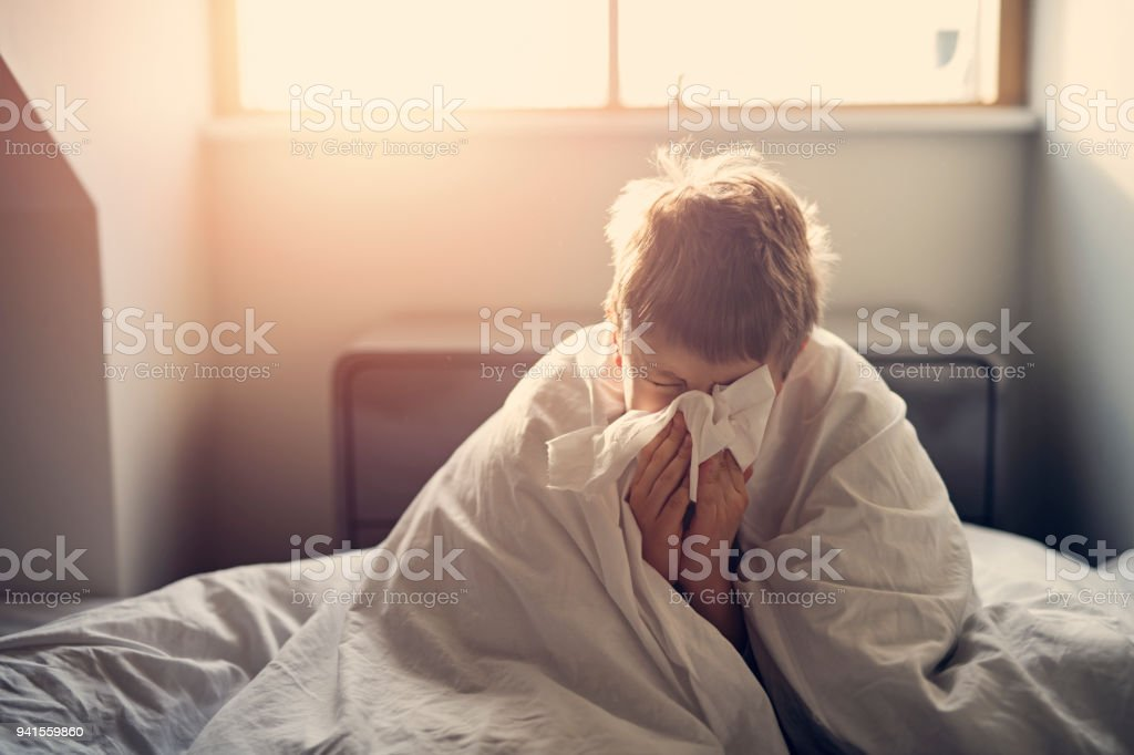 Sick little boy lying in bed and blowing nose stock photo