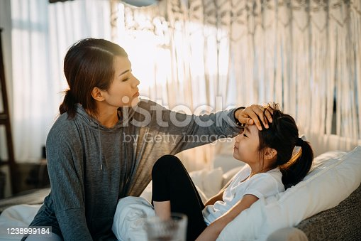 Sick little daughter lying in bed. Young Asian mother checking temperature on her forehead