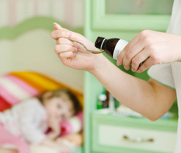 Sick little girl awaits her medication pouring in a spoon stock photo