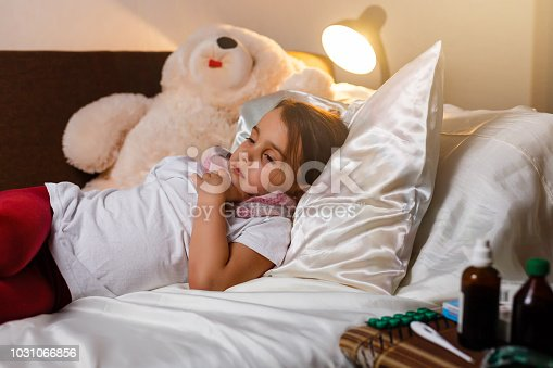 istock Sick little girl covered in blanket is hugging teddy bear and looking sadly on medicine while lying 1031066856