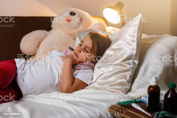 Sick little girl covered in blanket is hugging teddy bear and looking picture id1031066856?b=1&k=6&m=1031066856&s=612x612&h=sqezhuirl11aq95egs92zhhuhjoecctcjs6lcuy1ugc=
