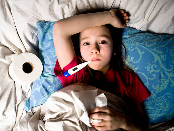 Sick Little Girl in Bed with Thermometer stock photo
