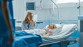 istock Sick Little Girl Lying in the Hospital Bed Sleeping, Her Mother Worries and Prays Beside Her. Emotional and Spiritual Moment Full of Hope. 1038800102