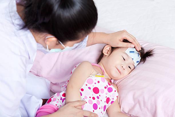 Sick little girl nursed by a pediatrician stock photo