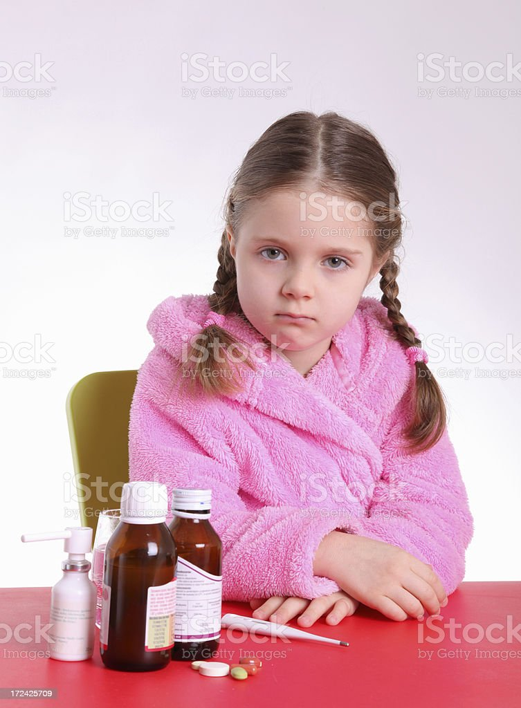 Sick little girl with medicines stock photo