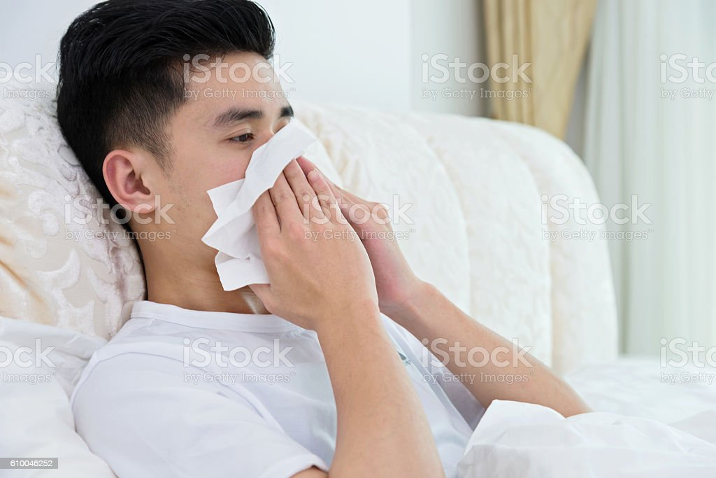 Sick man blowing his nose in bed stock photo