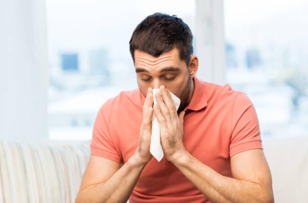 kranker Mann bläst Nase zu Papier Serviette zu Hause – Foto