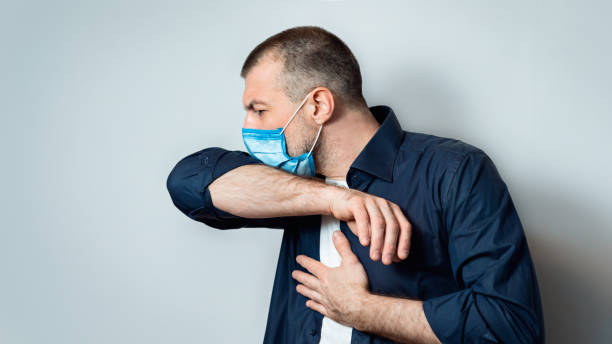 Sick Man Coughing Into Elbow Wearing Medical Mask, Gray Background stock photo