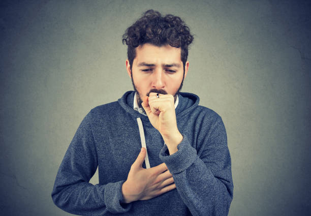 Sick man coughing with pain Young man having asthma problems and coughing badly covering mouth and holding hand on chest. heartburn throat pain stock pictures, royalty-free photos & images