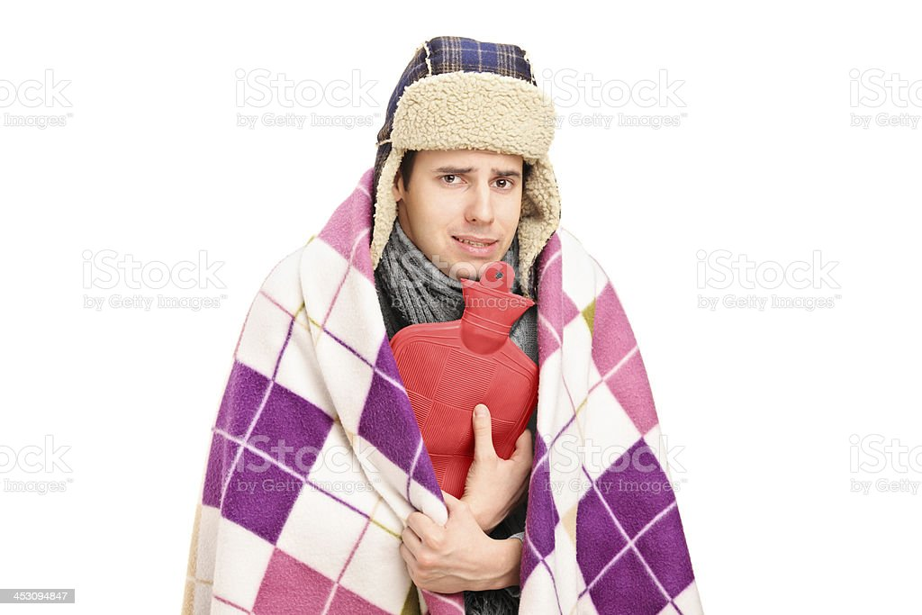 Sick man covered with blanket holding a hot-water bottle stock photo