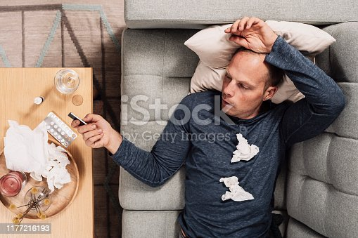 Sick man having a influensa cold Photo of mid adult man in sofa curing from cold, maby a man cold.