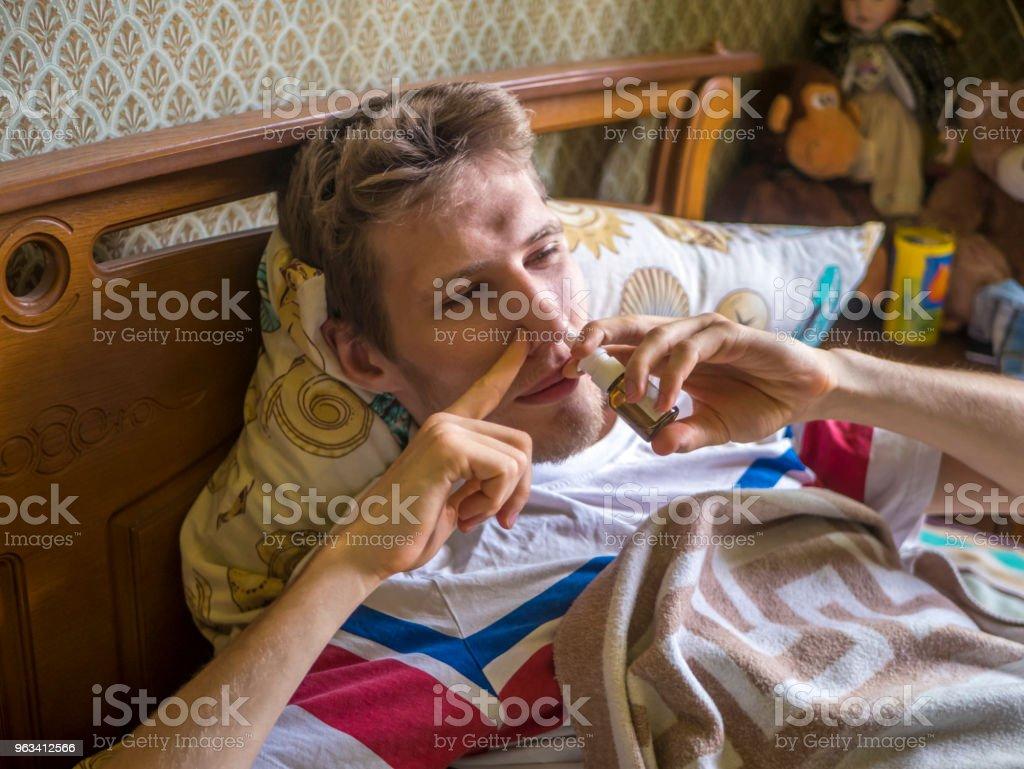 homme malade couché dans le lit avec suspension pour pulvérisation nasale - Photo de Adulte libre de droits