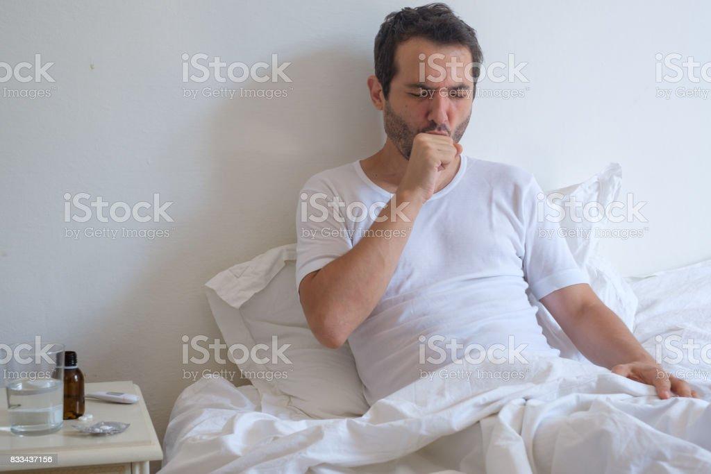 Hombre enfermo acostado en cama y tos - foto de stock