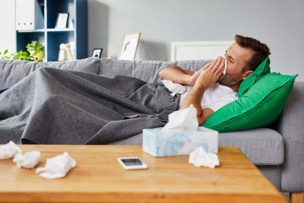kranker mann auf sofa zu hause liegen und nase - schnäuzen stock-fotos und bilder