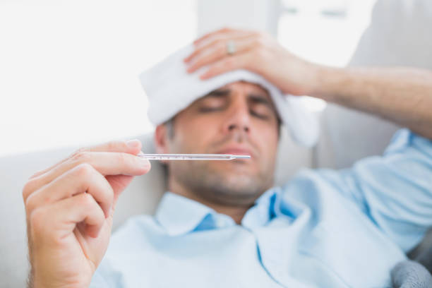 Sick man lying on sofa checking his temperature Sick man lying on sofa checking his temperature at home in the living room human parainfluenza virus stock pictures, royalty-free photos & images