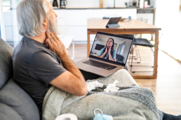 Sick Man on Video Call with Female Medical Consultant stock photo