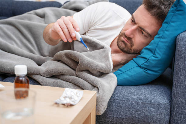 Sick man portrait on the sofa checking fever temperature stock photo