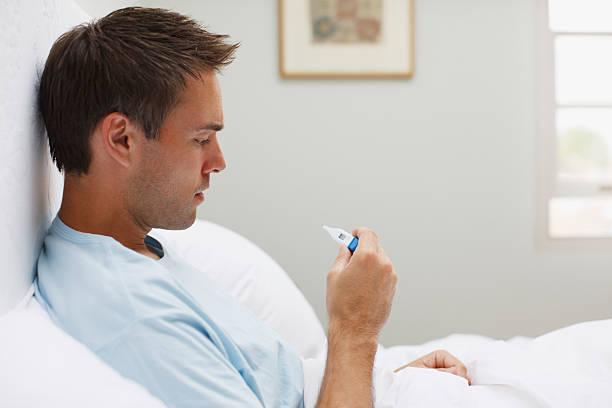 Hombre enfermo tomar la temperatura con un termómetro digital - foto de stock