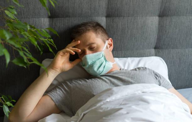 Sick man with medical mask lying in bed. Coronavirus quarantine concept. stock photo