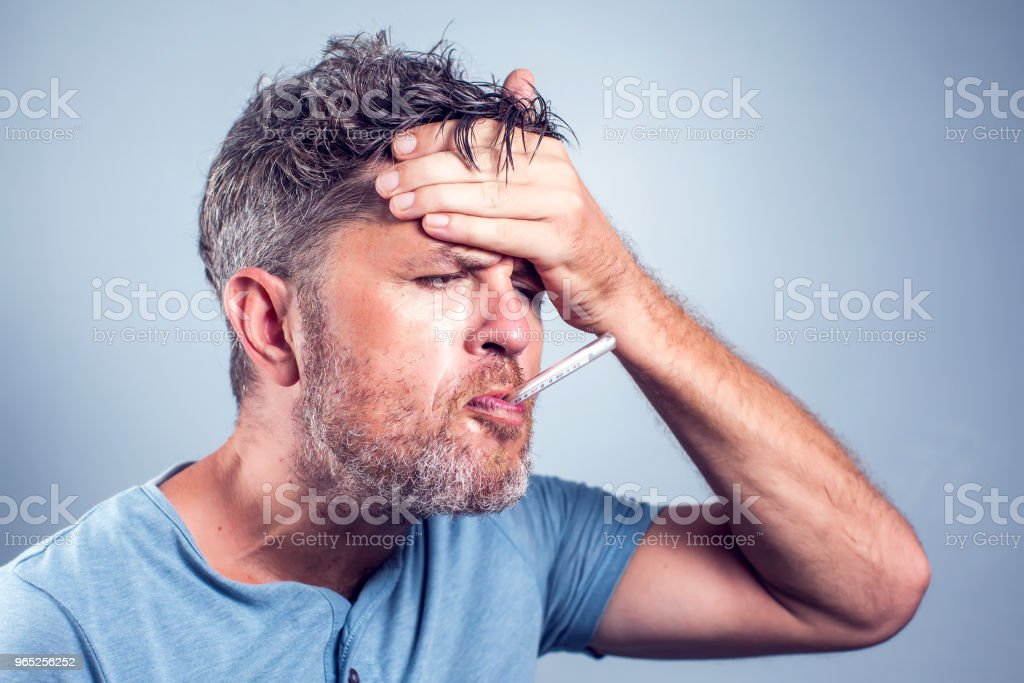 Sick man with thermometer in mouth,looking and worry at thermometer on white background,healthcare concept royalty-free stock photo