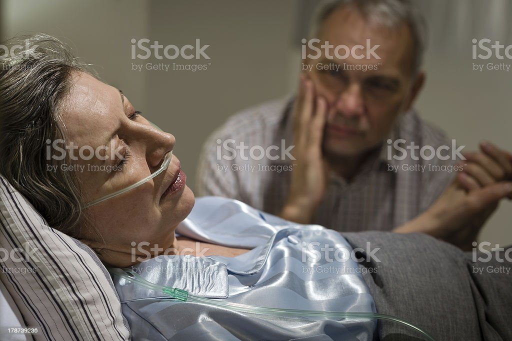 Sick mature woman lying in bed stock photo