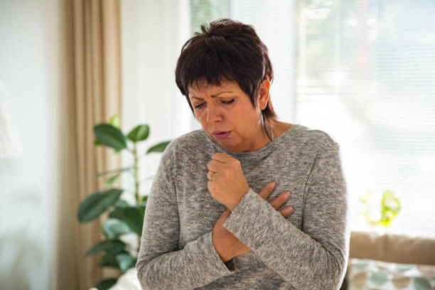 Sick mature woman with sore throat stock photo