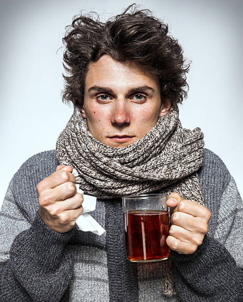 Sick men / Man Cold Man Cold / Ill young man with red nose, scarf, sneezing into handkerchief. Medication or drugs abuse, healthcare concept cold virus stock pictures, royalty-free photos & images
