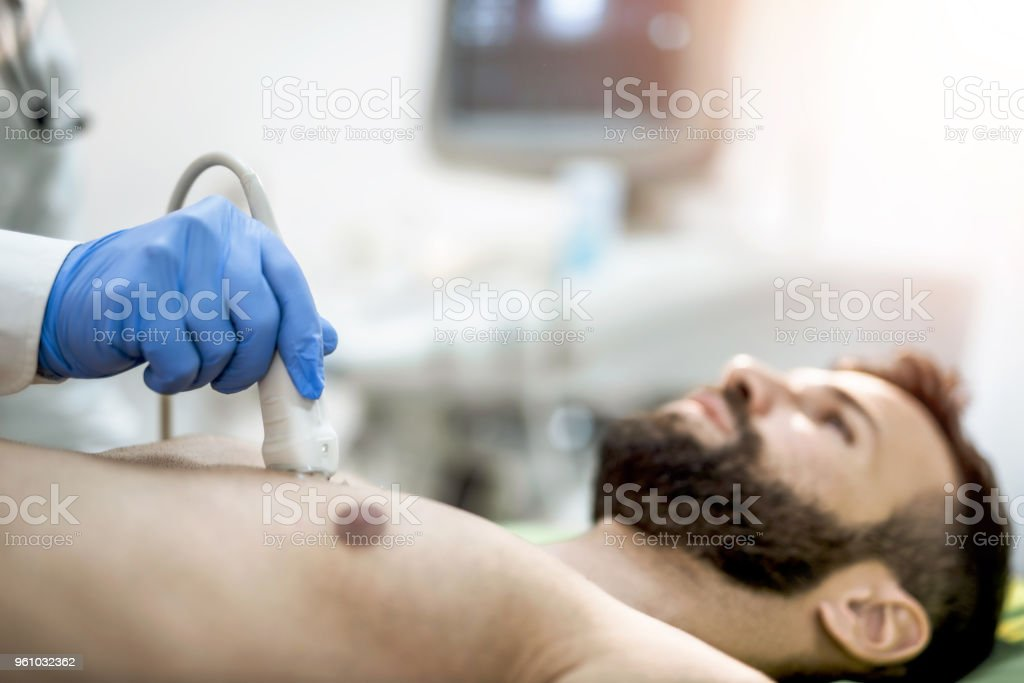 Sick mid adult man having his chest examined by ultrasound technology. stock photo