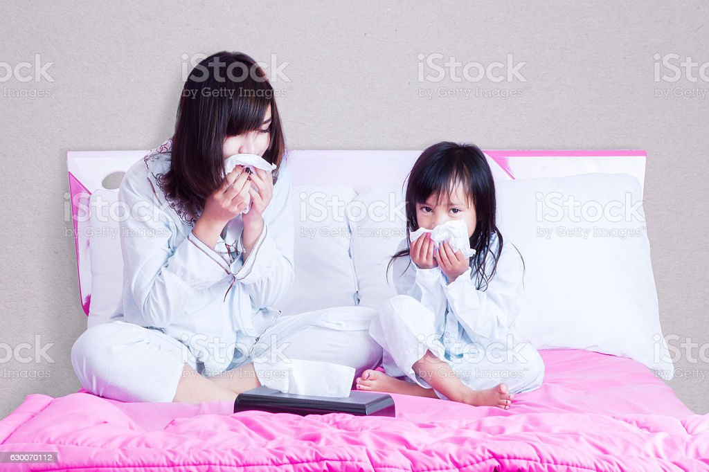Sick mother and child wiping their nose stock photo