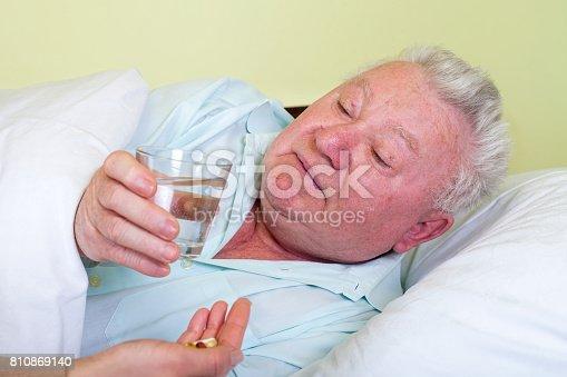 istock Sick old man in bed, receiving his pills 810869140