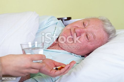istock Sick old man in bed, receiving his pills 852039256