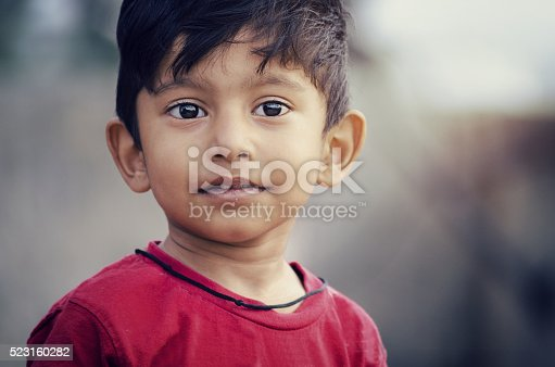 indian asian sick poor boy child portrait looking sideways with soar thirsty lips outdoor at sunrise or sunset