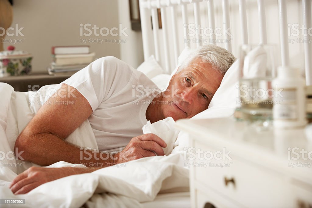 Sick Senior Man In Bed At Home stock photo