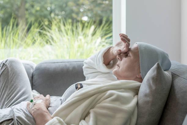 sjuka äldre med en hand på en panna som liggande på en soffa - kronisk sjukdom bildbanksfoton och bilder
