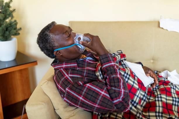 Sick Senior avec une pneumonie utilise Inhaler - Photo