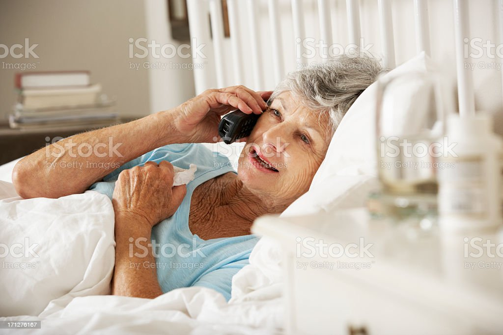 Sick Senior Woman In Bed At Home Talking On Phone stock photo