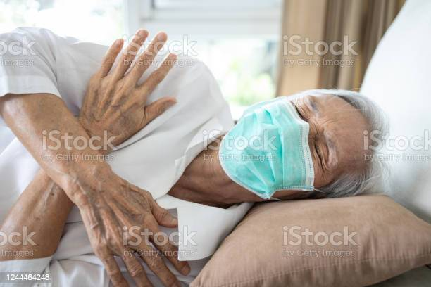 Sick Senior Woman Wear A Mask Has A Fevershiveringhigh Temperaturechillyold People Have A Coldflutired Elderly Patient With Muscle Pain All Over The Bodyaches From Fever Coronavirus Infection Stock Photo - Download Image Now