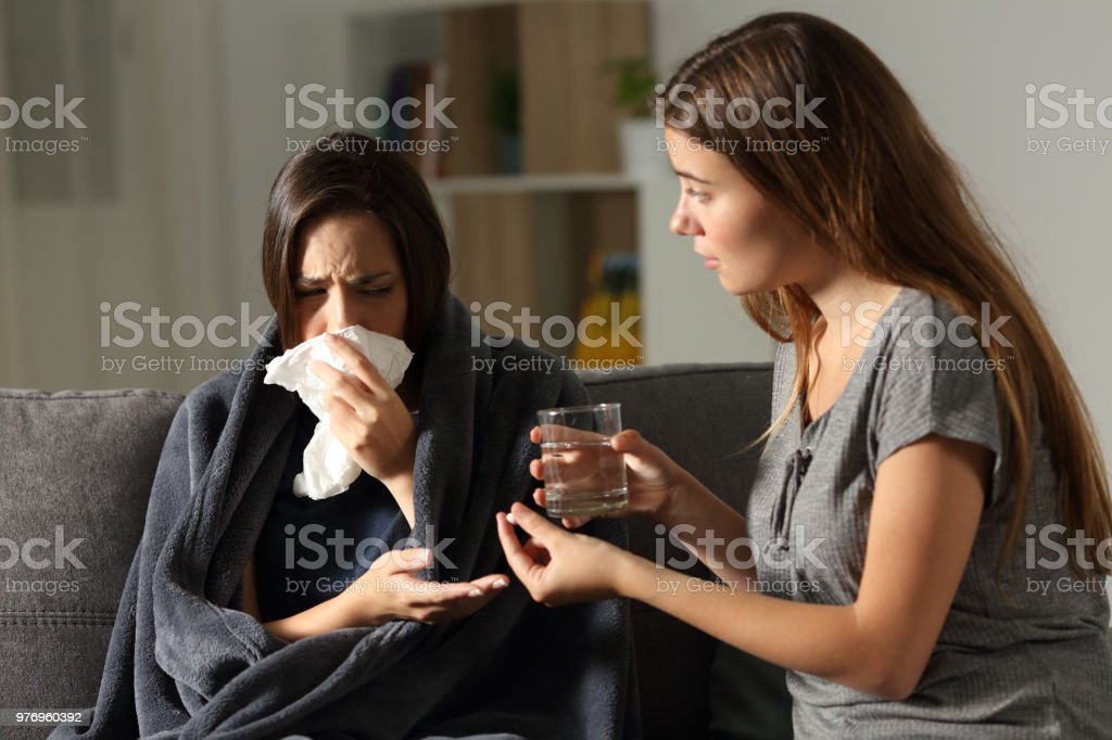 Sick woman and her friend giving painkiller pill stock photo