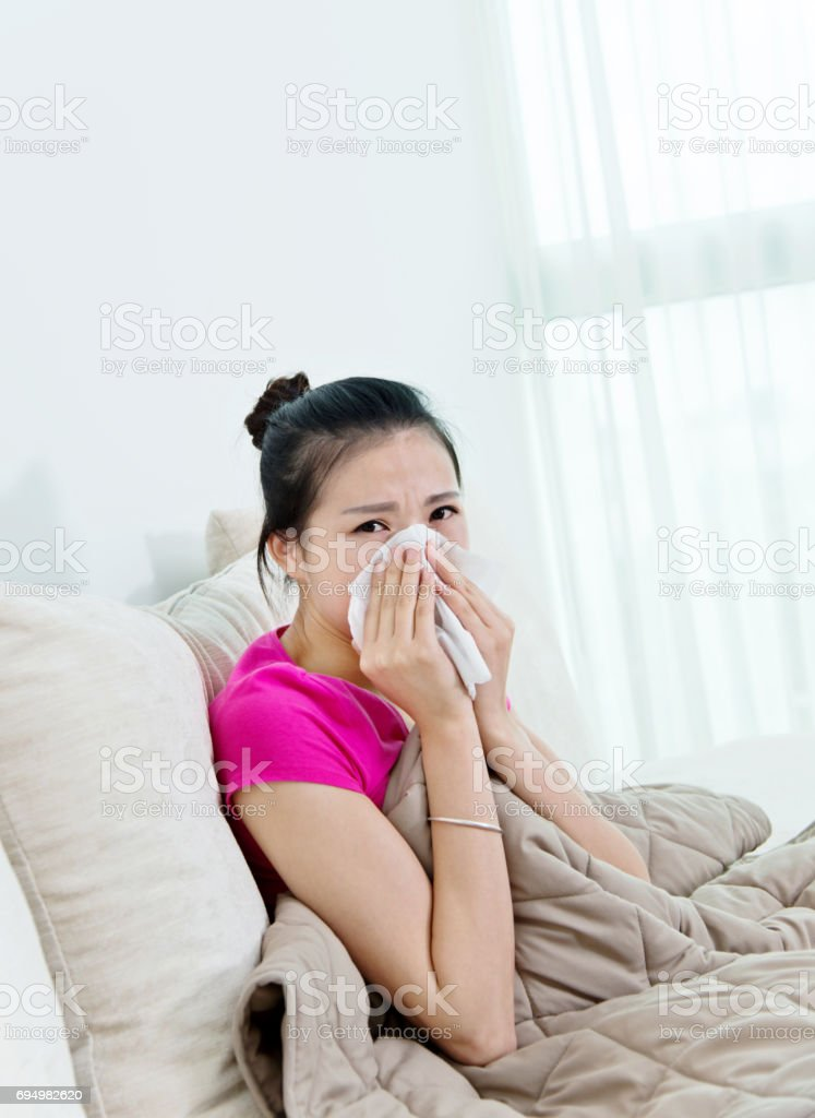 Sick woman blowing her nose on sofa stock photo