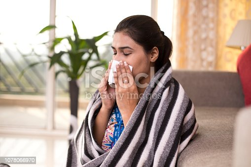 Sick woman sitting at home and blowing her nose