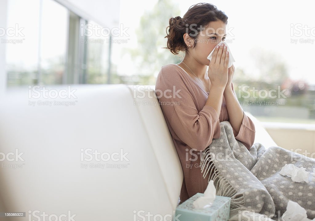 Sick woman blowing her nose  30-34 Years Stock Photo