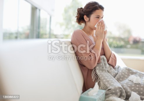 istock Sick woman blowing her nose 135385322