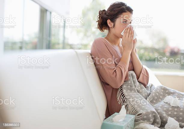 Sick Woman Blowing Her Nose Stock Photo - Download Image Now