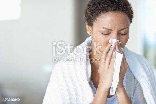 istock Sick woman blowing her nose 170510649