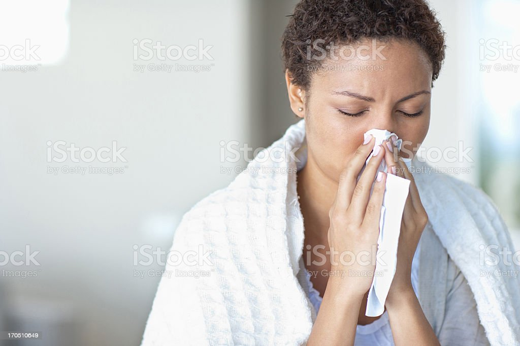 Sick woman blowing her nose stock photo
