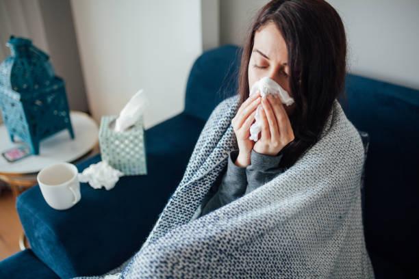 sick woman blowing her nose, she covered with blanket - condizione medica foto e immagini stock