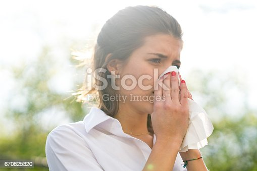 istock Sick woman blowing his nose into tissue, outdoors 670825320