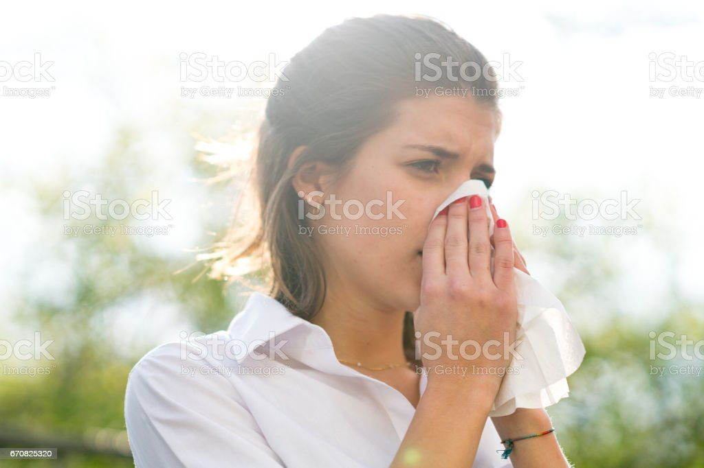 Sick woman blowing his nose into tissue, outdoors stock photo
